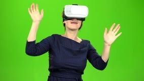 La mujer en vidrios virtuales está mirando una película interesante Pantalla verde almacen de video