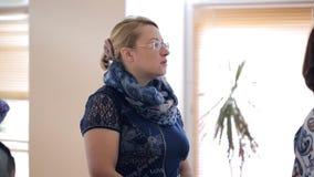 La mujer en vidrios y bufanda se coloca y escucha la ventana metrajes
