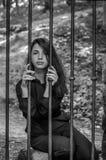 La mujer encantadora joven con el delincuente largo del pelo, se sienta detrás de barras en el viejo preso de piedra de la cárcel Fotografía de archivo libre de regalías