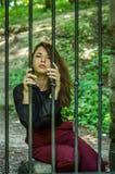 La mujer encantadora joven con el delincuente largo del pelo, se sienta detrás de barras en el viejo preso de piedra de la cárcel Imagen de archivo libre de regalías