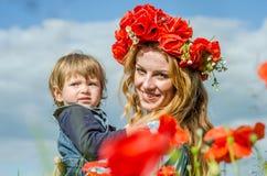 La mujer encantadora joven con la mamá larga del pelo con su hija en sus brazos que camina en campo de la amapola con un ramo de  Imágenes de archivo libres de regalías