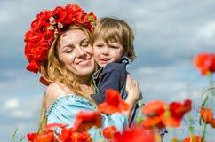 La mujer encantadora joven con la mamá larga del pelo con su hija en sus brazos que camina en campo de la amapola con un ramo de  Fotos de archivo libres de regalías