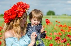 La mujer encantadora joven con la mamá larga del pelo con su hija en sus brazos que camina en campo de la amapola con un ramo de  Fotografía de archivo libre de regalías