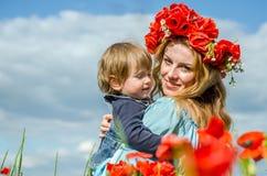La mujer encantadora joven con la mamá larga del pelo con su hija en sus brazos que camina en campo de la amapola con un ramo de  Foto de archivo libre de regalías