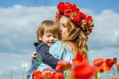 La mujer encantadora joven con la mamá larga del pelo con su hija en sus brazos que camina en campo de la amapola con un ramo de  Imagen de archivo