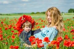 La mujer encantadora joven con la mamá larga del pelo con su hija en sus brazos que camina en campo de la amapola con un ramo de  Foto de archivo