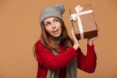 La mujer encantadora joven en rojo hizo punto el suéter que sostenía la caja de regalo, lo Imágenes de archivo libres de regalías