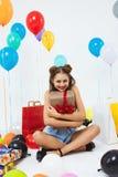 La mujer encantadora se sienta en la posición de loto que sostiene la caja de regalo grande Fotografía de archivo libre de regalías