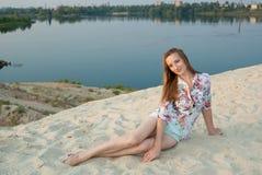 La mujer encantadora sonríe en la arena cerca del lago de la ciudad Fotografía de archivo