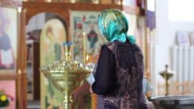 La mujer enciende una vela y ruega en la iglesia ortodoxa almacen de video