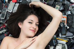 Mujer encima de una pila de teléfonos celulares móviles fotos de archivo