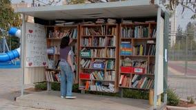 La mujer encuentra un libro interesante en la biblioteca de la calle en Israel metrajes