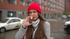 La mujer enferma femenina joven, muchacha utiliza un espray de nariz en la calle afuera, atención sanitaria, gripe, gente, salud, almacen de metraje de vídeo