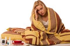 La mujer enferma que se sienta en el malo envuelto en una enfermedad combinada de la sensación, tiene Imagen de archivo libre de regalías