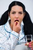 La mujer enferma toma una píldora Fotografía de archivo libre de regalías