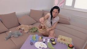 La mujer enojada con los oídos del conejito acerca a la tabla con los huevos de Pascua