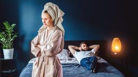 La mujer enojada en albornoz se coloca en dormitorio, sus brazos cruzados sobre hombre del pecho está mintiendo en cama Pares que fotografía de archivo libre de regalías