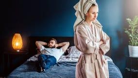 La mujer enojada en albornoz se coloca en dormitorio, sus brazos cruzados sobre hombre del pecho está mintiendo en cama Pares que foto de archivo libre de regalías