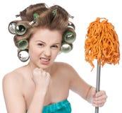 La mujer enojada en rodillos del pelo es esponja de la explotación agrícola Fotografía de archivo