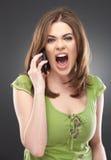 La mujer enojada grita en el teléfono aislado en gris Fotos de archivo libres de regalías