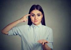 ¿La mujer enojada que gesticula con el finger contra el templo es usted loco? Foto de archivo libre de regalías
