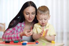La mujer enseña a artesanía del niño imagenes de archivo