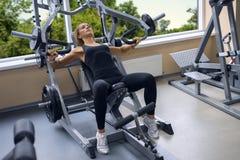 La mujer entrena a Pecs en el gimnasio Imagen de archivo libre de regalías