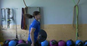 La mujer entrena a posiciones en cuclillas en el centro del crossfit Muchacha adulta joven que hace posiciones en cuclillas resis almacen de metraje de vídeo