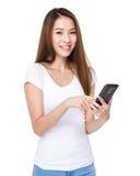 La mujer envía el mensaje en el teléfono móvil fotos de archivo libres de regalías