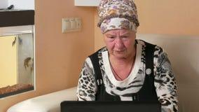 La mujer envejeció el trabajo en el ordenador portátil en casa en el sofá Ella mira fijamente la pantalla y pulsa la tecla Al lad almacen de video