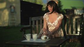 La mujer envejecida centrode está bebiendo el té que se sienta en un banco en la puesta del sol almacen de metraje de vídeo