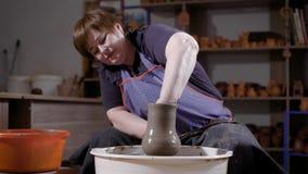 La mujer envejecida centro está haciendo el florero de cerámica usando la rueda de alfareros que se sienta en el taller oscuro de metrajes