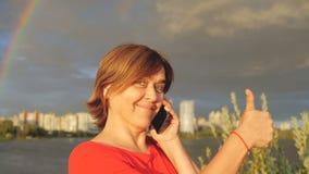La mujer envejecida centro feliz muestra el pulgar y habla con el teléfono en la cámara lenta metrajes