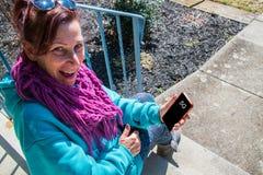 La mujer envejecida centro sonriente feliz se est? sentando en los pasos que sostienen un smartphone La pantalla dice 5G foto de archivo