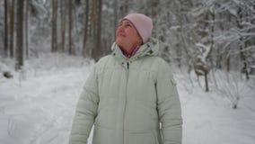 La mujer envejecida feliz está caminando en la trayectoria en el bosque que respira el aire fresco y la sonrisa El viajero femeni almacen de metraje de vídeo