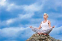 La mujer envejecida madura hermosa se sienta encima de un acantilado que hace yoga Fotografía de archivo