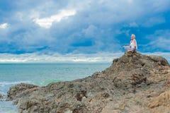 La mujer envejecida madura hermosa se sienta encima de un acantilado que hace yoga Imágenes de archivo libres de regalías