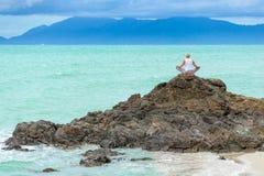 La mujer envejecida madura hermosa se sienta encima de un acantilado que hace yoga Fotos de archivo libres de regalías