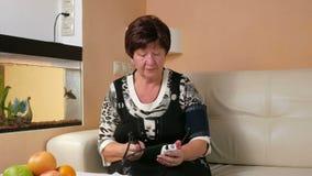 La mujer envejecida mide la presión arterial en casa Ella lleva un puño y el testimonio del aparato médico mira de cerca metrajes