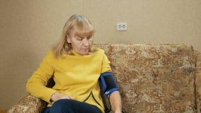 La mujer envejecida mide la presión de su propio hogar en el sofá Ella escucha el pulso a través del sphygmomanometer almacen de video