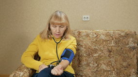 La mujer envejecida mide la presión de su propio hogar en el sofá Ella escucha el pulso a través del sphygmomanometer metrajes
