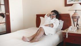 La mujer envejecida miente en una cama en un hotel en una albornoz blanca y controla la TV usando el telecontrol r almacen de metraje de vídeo