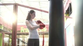 La mujer envuelve sus manos con una cinta del boxeo en un gimnasio de moda en la puesta del sol almacen de video