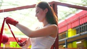 La mujer envuelve sus manos con una cinta del boxeo en un gimnasio de moda en la puesta del sol Ciérrese encima del MES lento metrajes