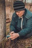 La mujer envuelve un ?rbol del injerto con una cinta aislante en el jard?n para detener la humedad en ella en primer imagen de archivo libre de regalías