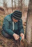 La mujer envuelve un ?rbol del injerto con una cinta aislante en el jard?n para detener la humedad en ella en primer fotos de archivo libres de regalías