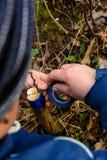 La mujer envuelve un ?rbol del injerto con una cinta aislante en el jard?n para detener la humedad en ella en primer fotos de archivo