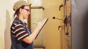 La mujer es electricista y anota las lecturas de los instrumentos en el cuarto eléctrico almacen de metraje de vídeo