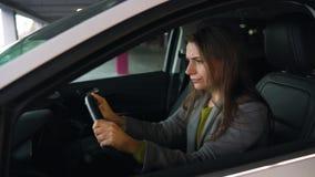 La mujer es enojada y de derrota de su cabeza en el volante, porque su coche analizado almacen de video
