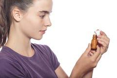 La mujer es examina una botella de medicina homeopática Foto de archivo